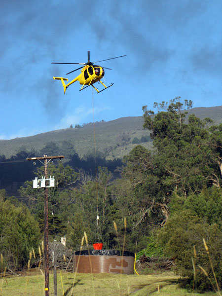 A Windward Aviation helicopter dips water from a ranch tank.